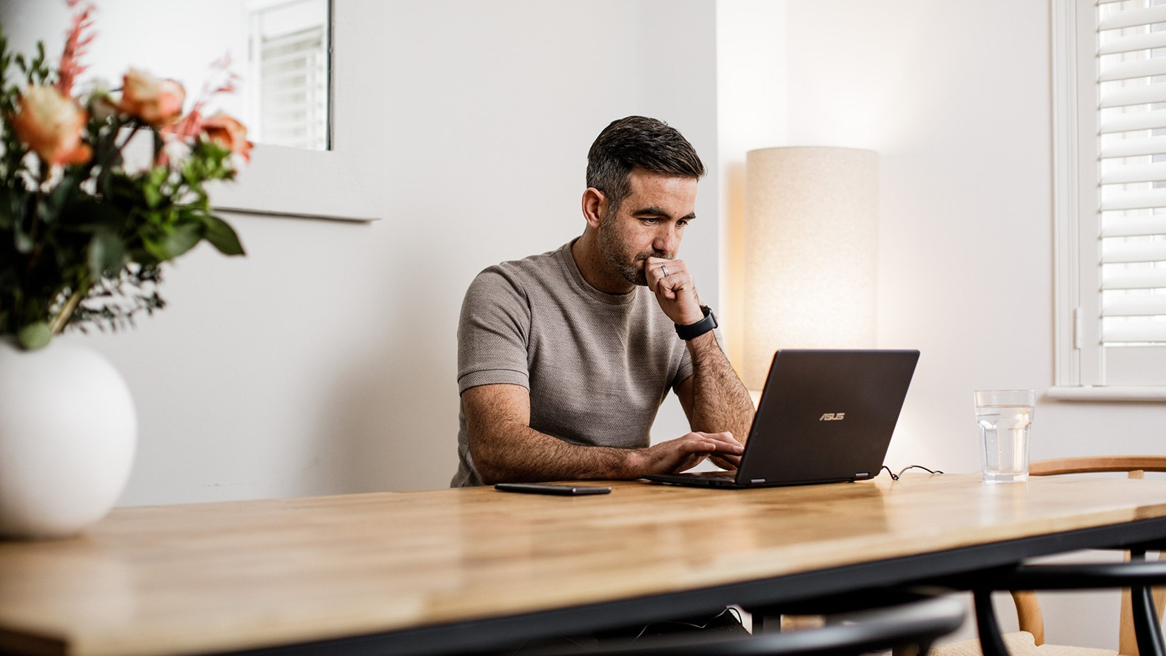 Man searches on a laptop whilst sat at the kitchen table.