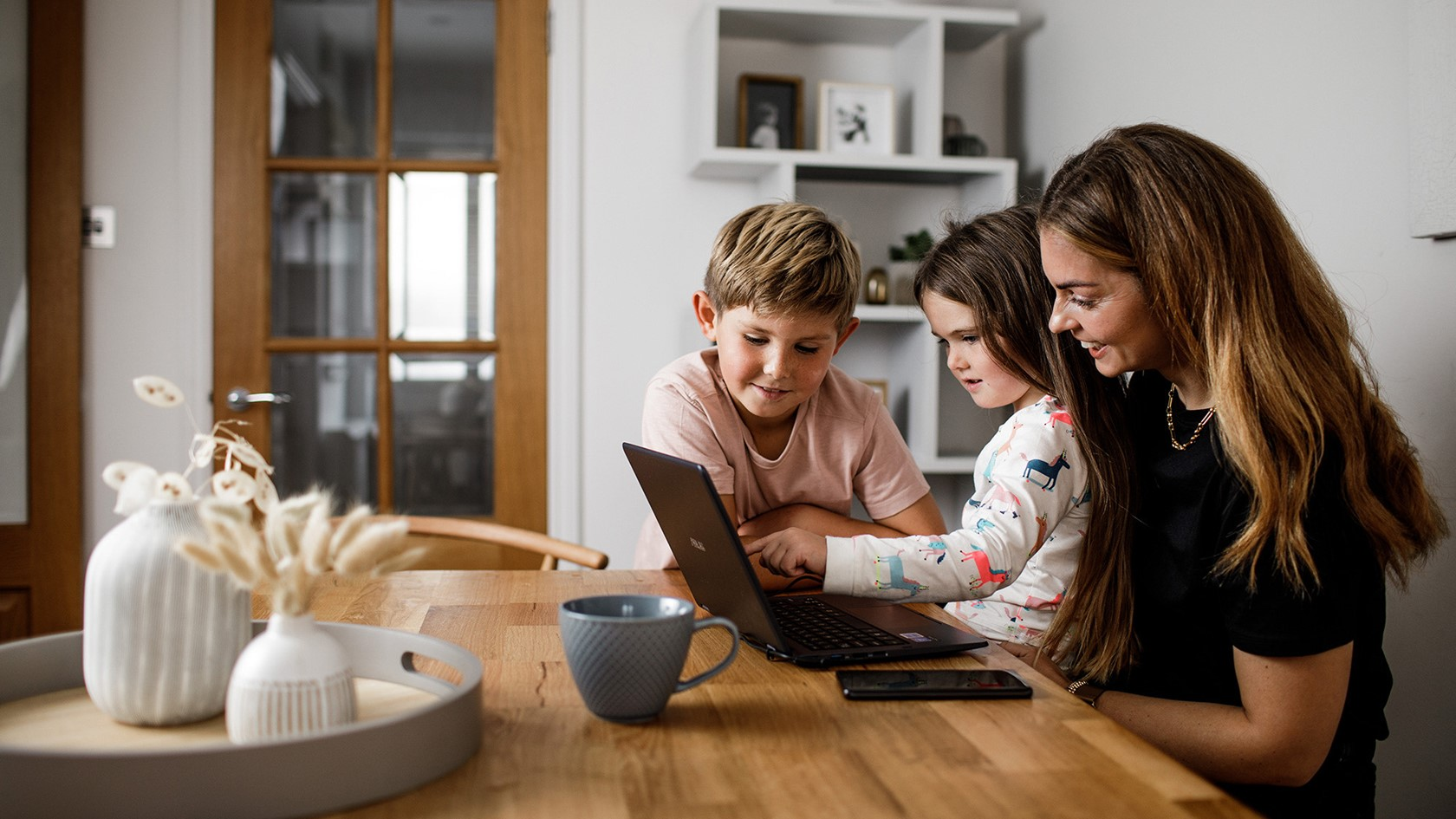 A mother and her children sat at the kitchen table enjoying something on a laptop computer.