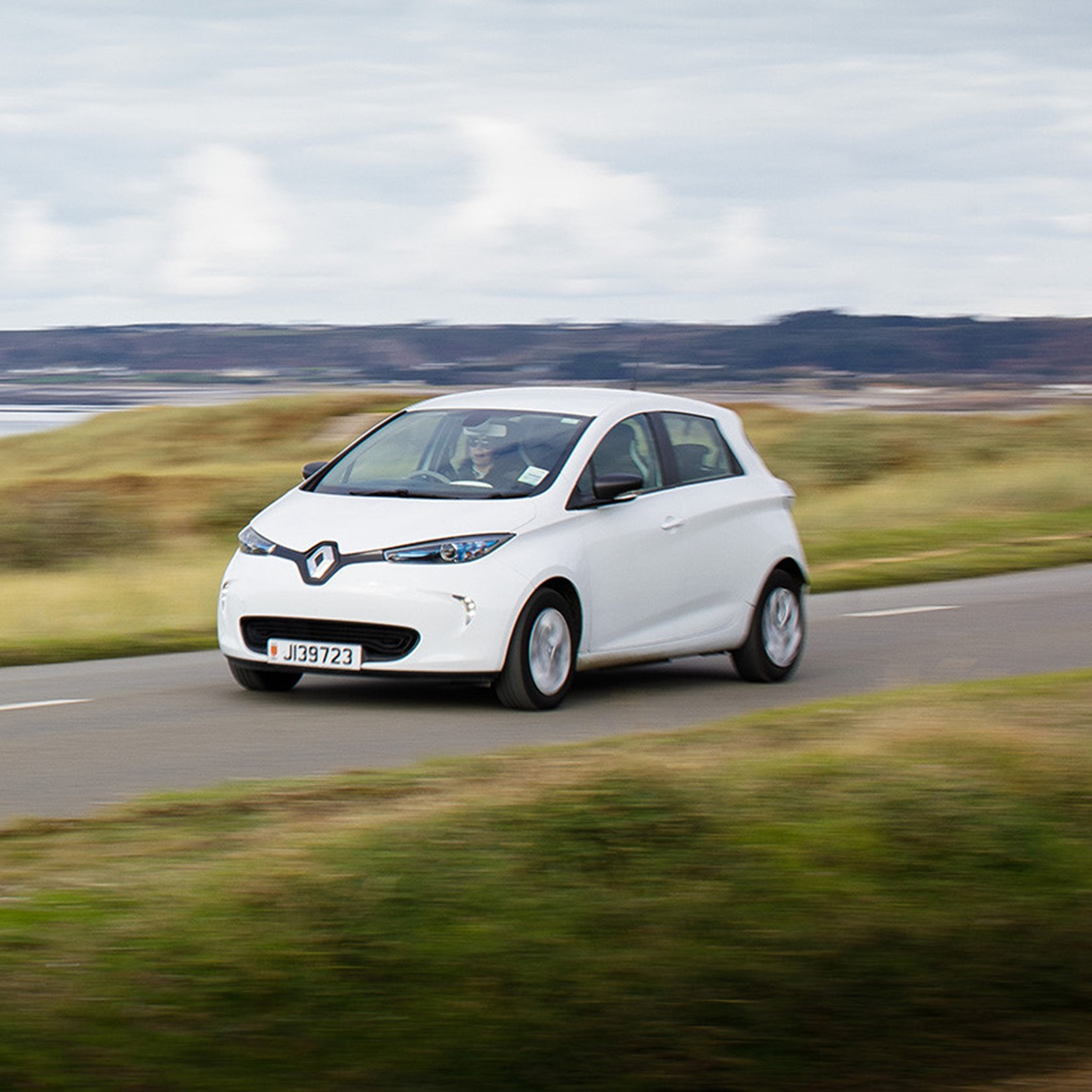 An electric vehicle speeds across the Five Mile Road in St Ouen on a cloudy covered day.