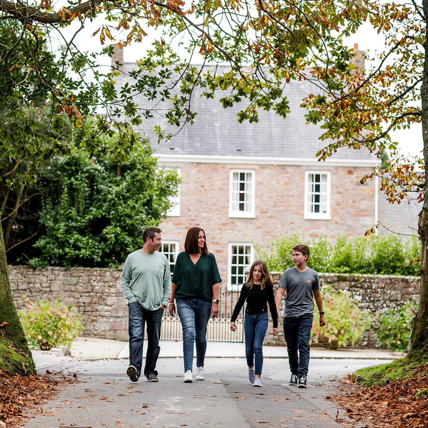 A family walk past a period house in the Jersey countryside.