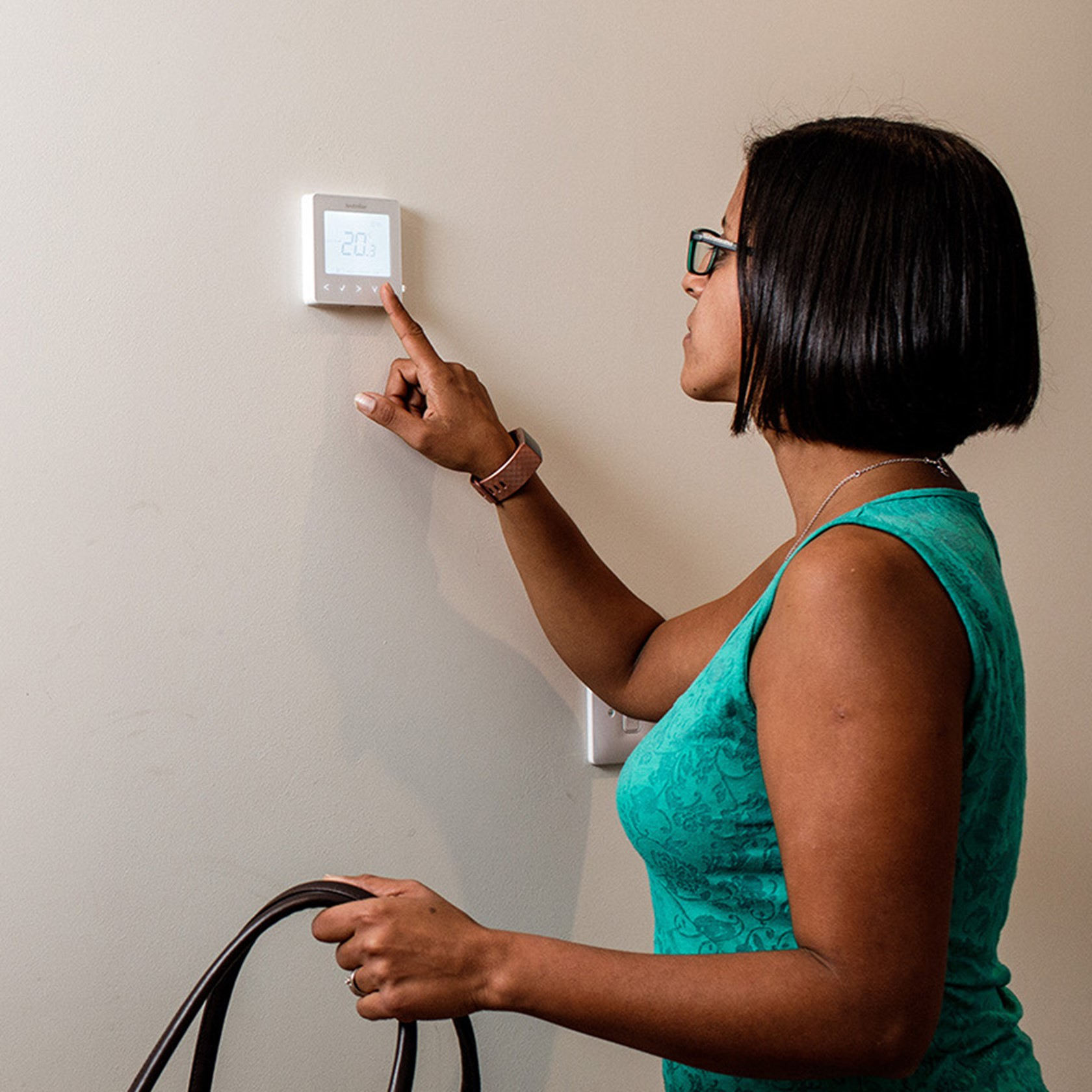 A woman holds a large bag whilst adjusting her electric heating thermostat.