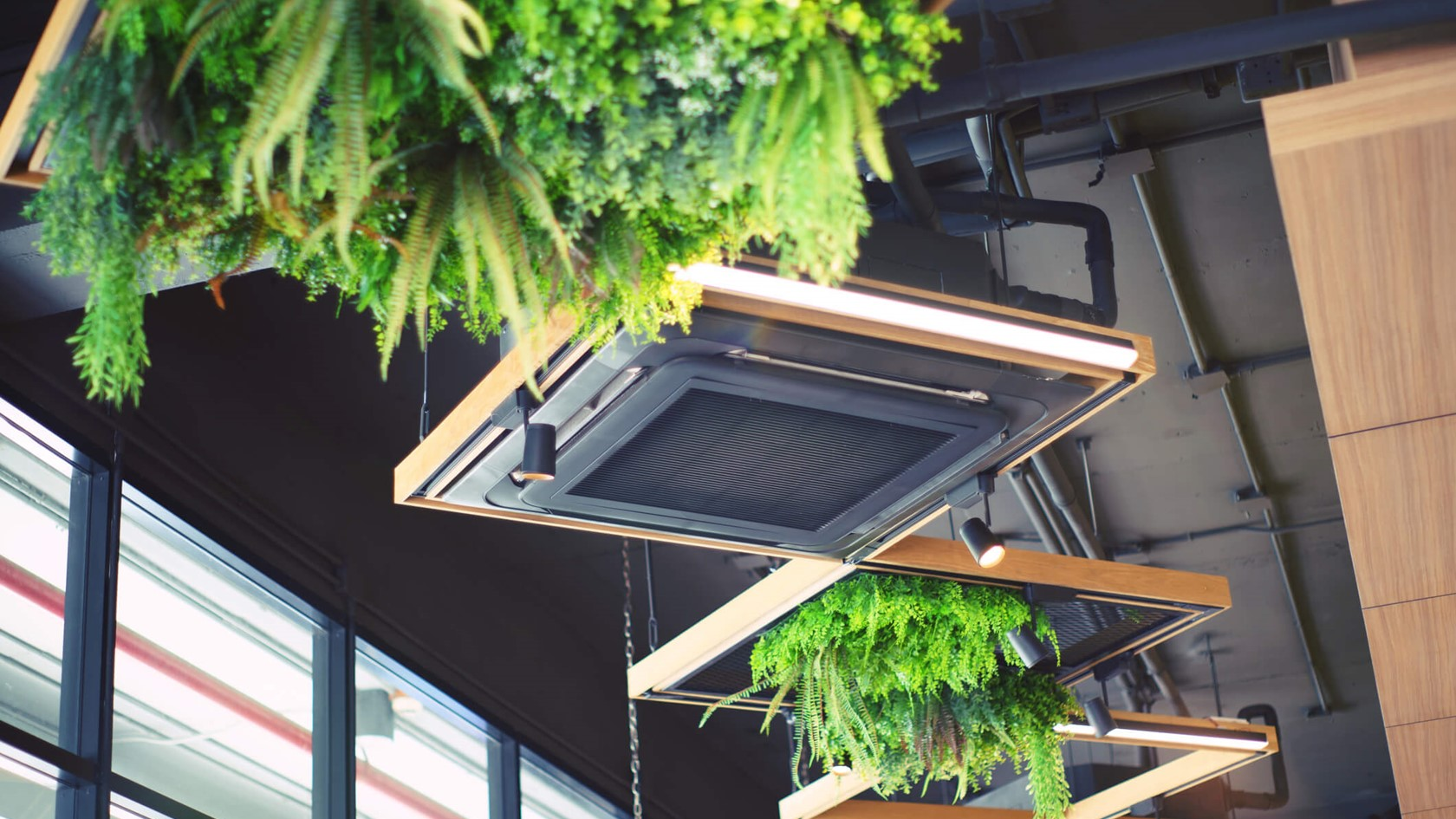 An electric commercial heater unit hangs from the ceiling in a modern cafe.