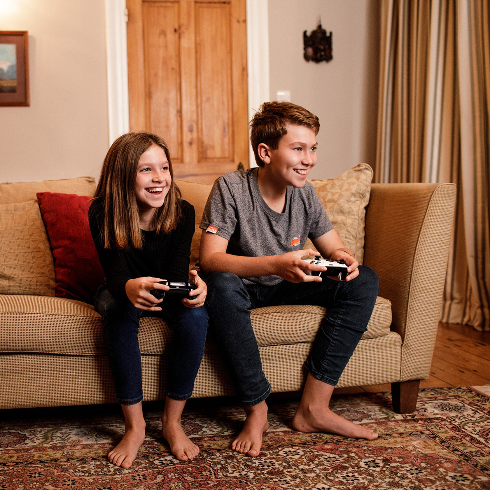 A brother and sister sit on the sofa and play video games.