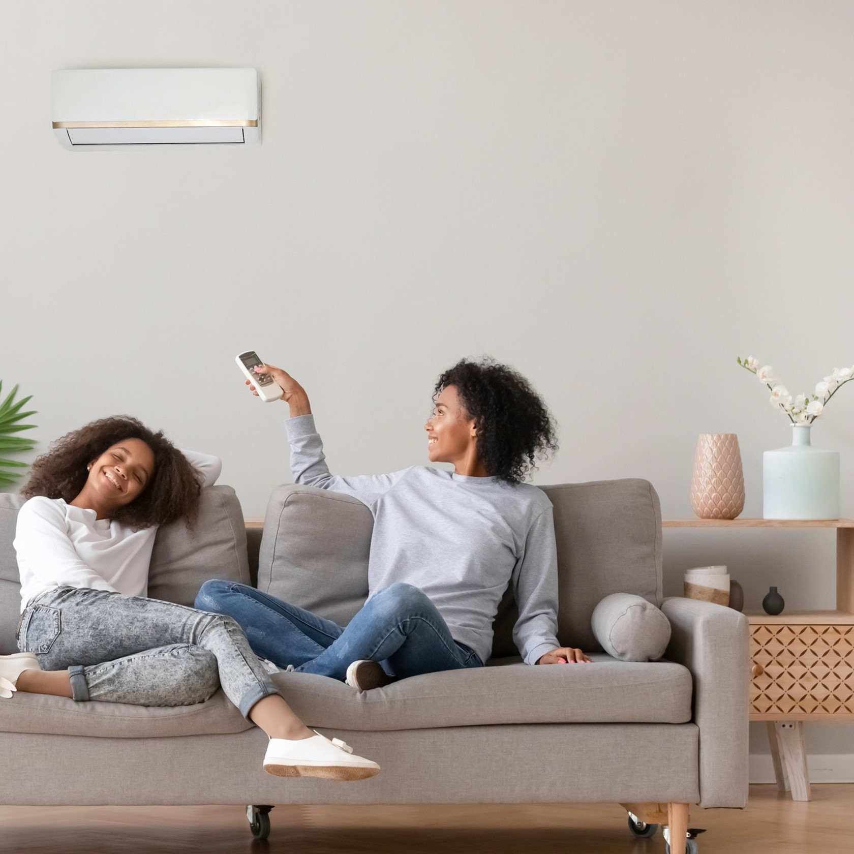 A mother and daughter sit on a couch in a modern home. The mother is operating her air conditioning unit with the remote.