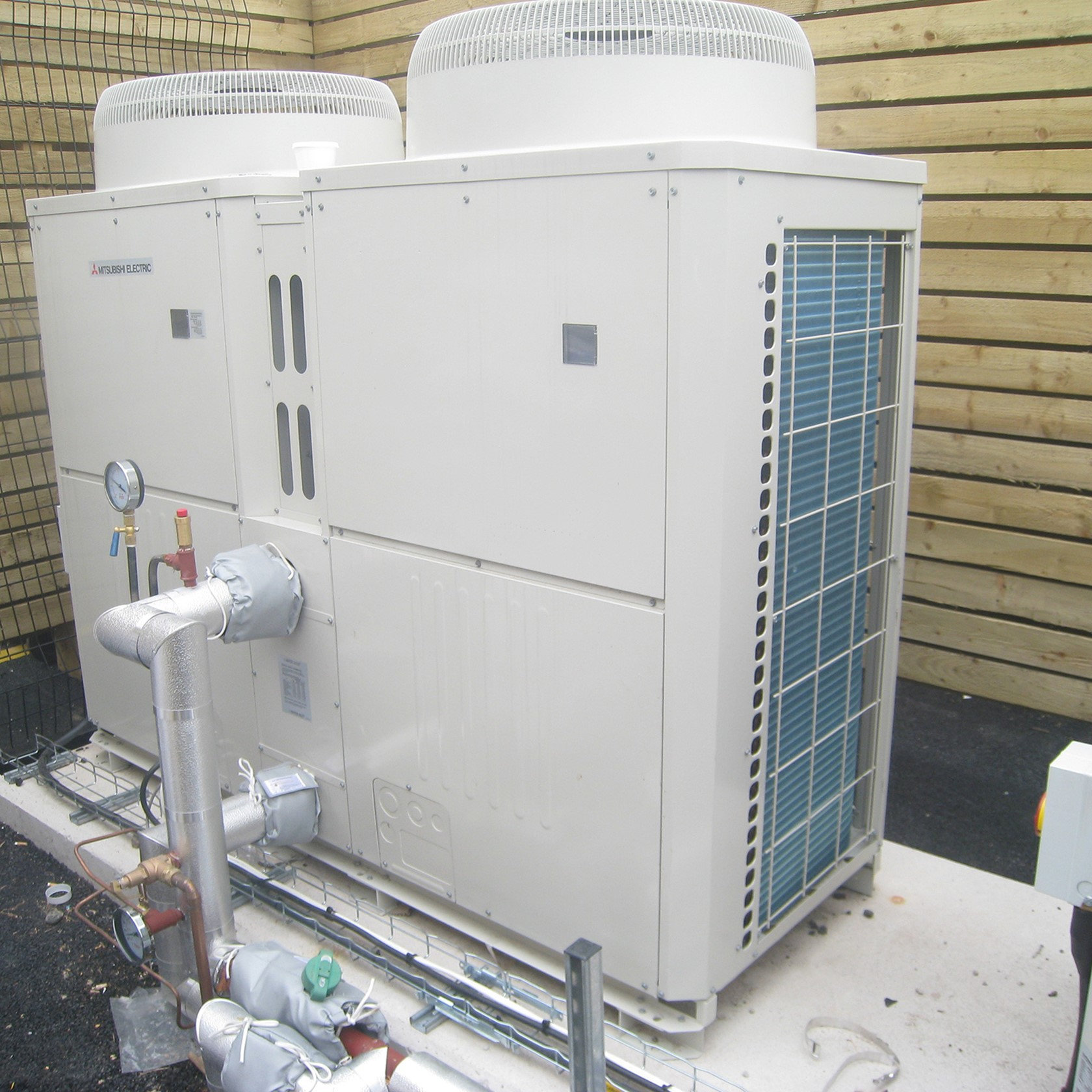A commercial heat pump system installed in a custom built area.