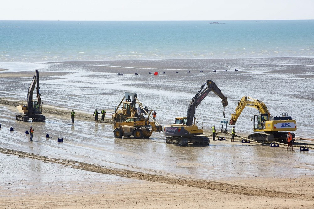 Excavators on the beach lift the Normandie 3 subsea cable into place.