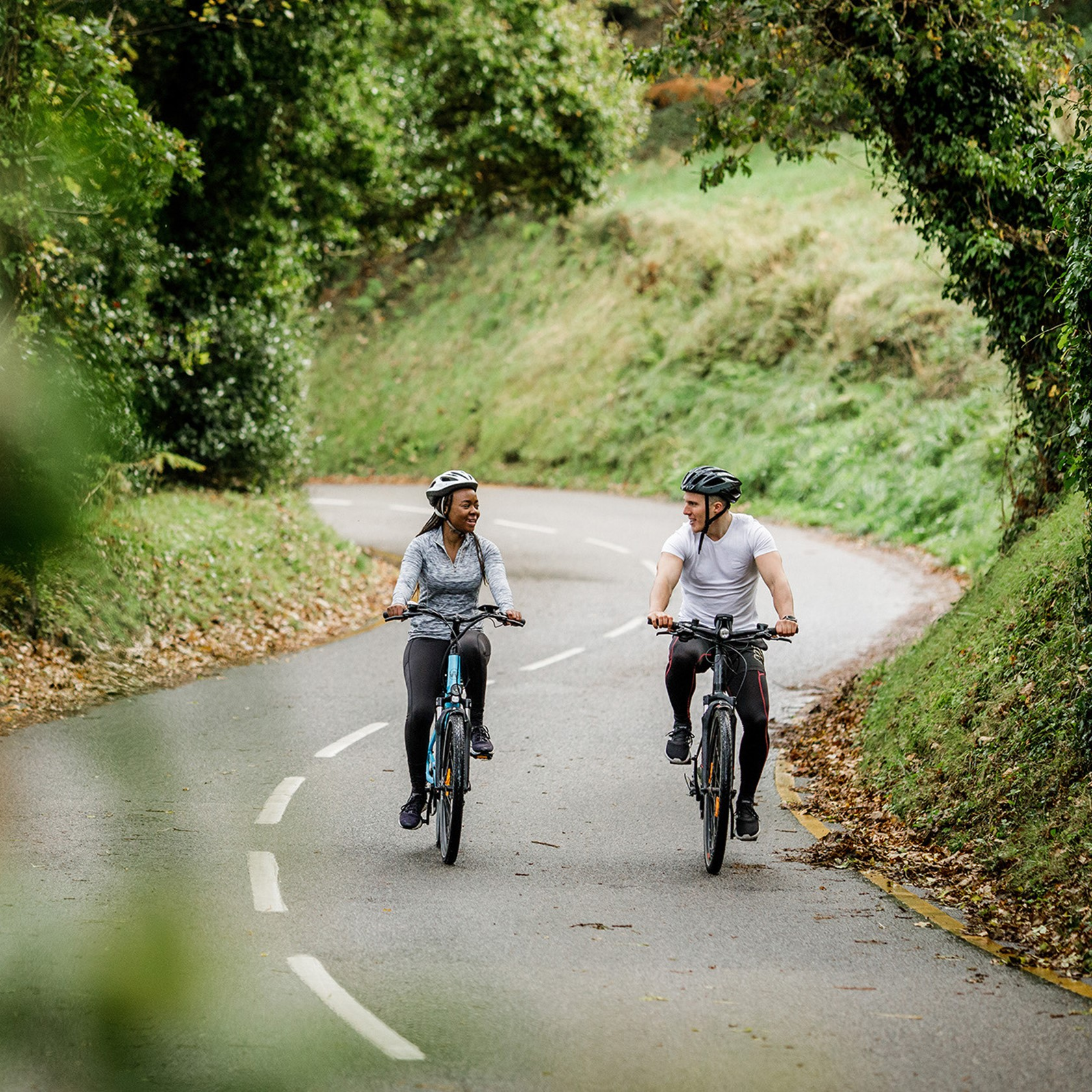 A man and a women cycle electric bicycles through Jersey's country lanes