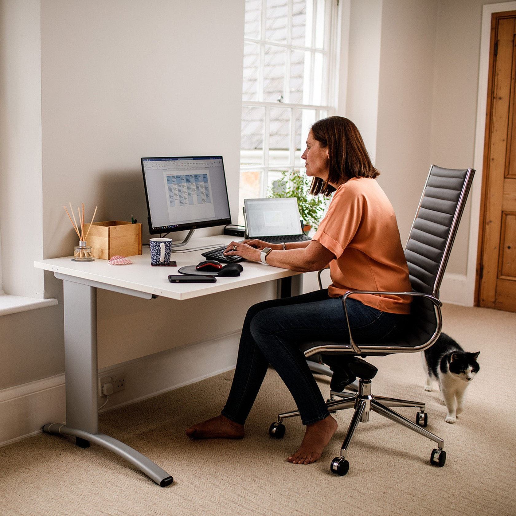 A woman uses a computer in a cosy looking home office.