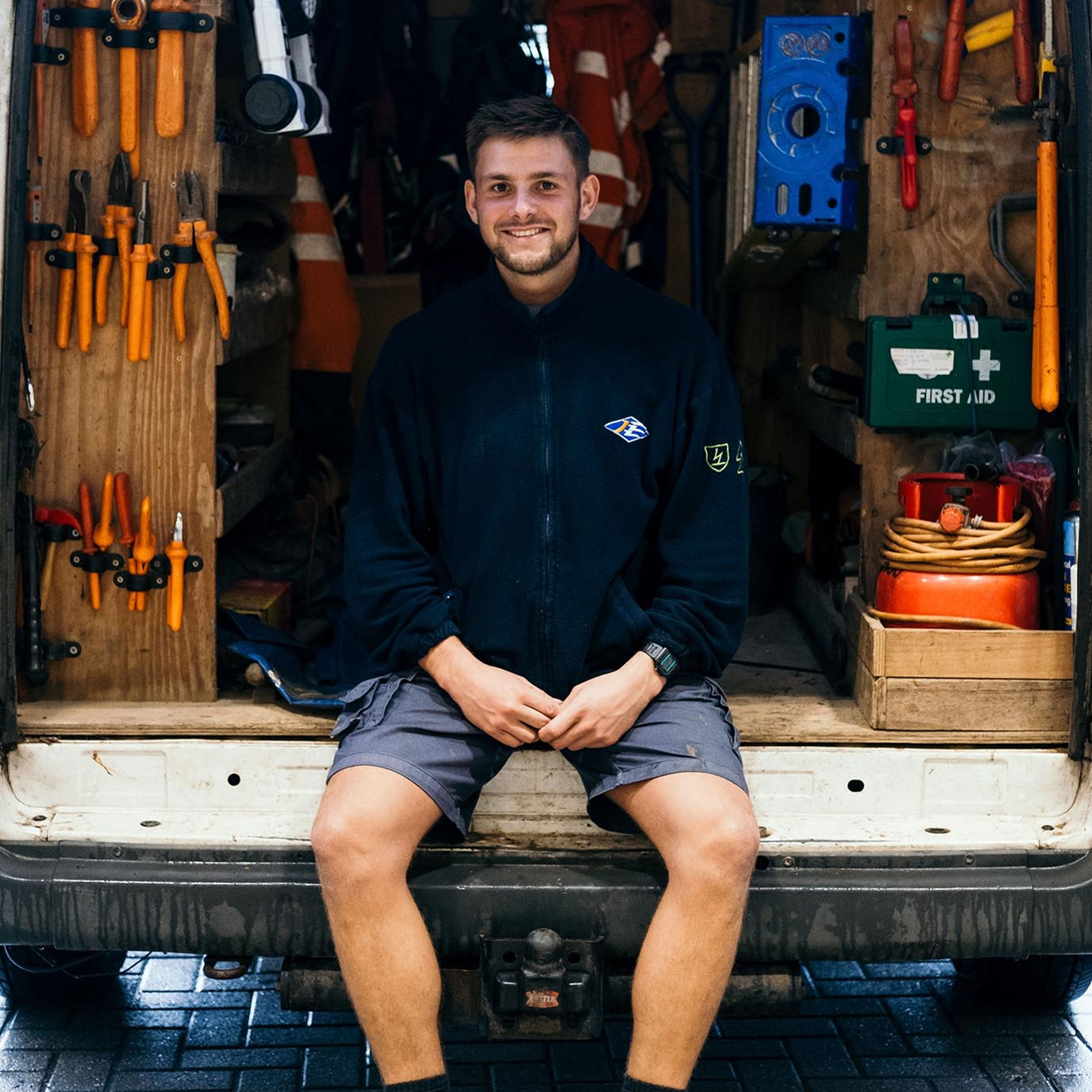 A Jersey Electricity Apprentice sits in the back of a van.