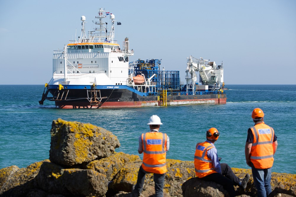 Three members of the Normandie 1 project team watch as Stemat arrives in Jersey.