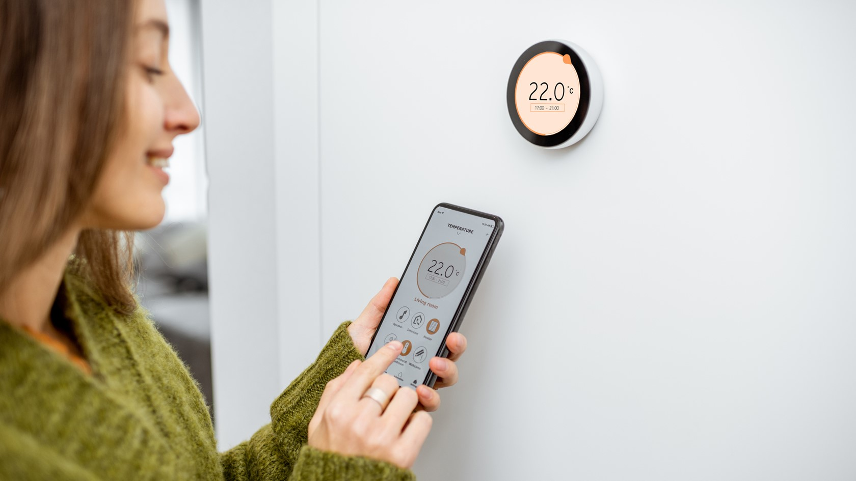 A young woman uses her phone to control her smart heating system.