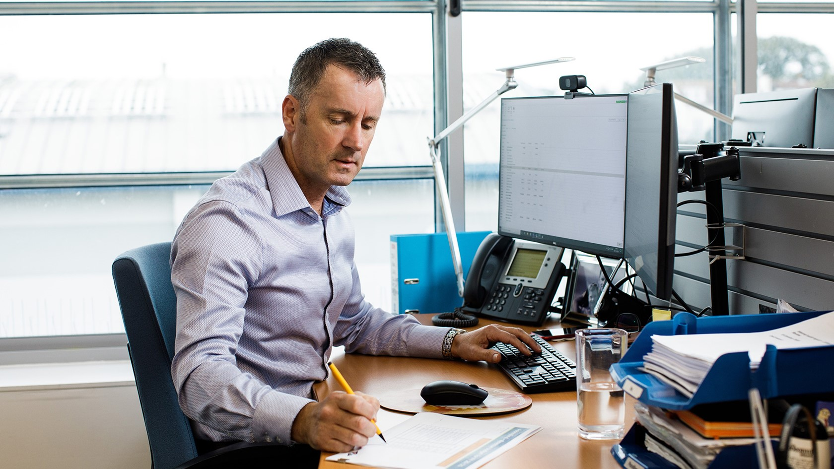 Andy Kemp works at his desk at the Jersey Electricy offices.