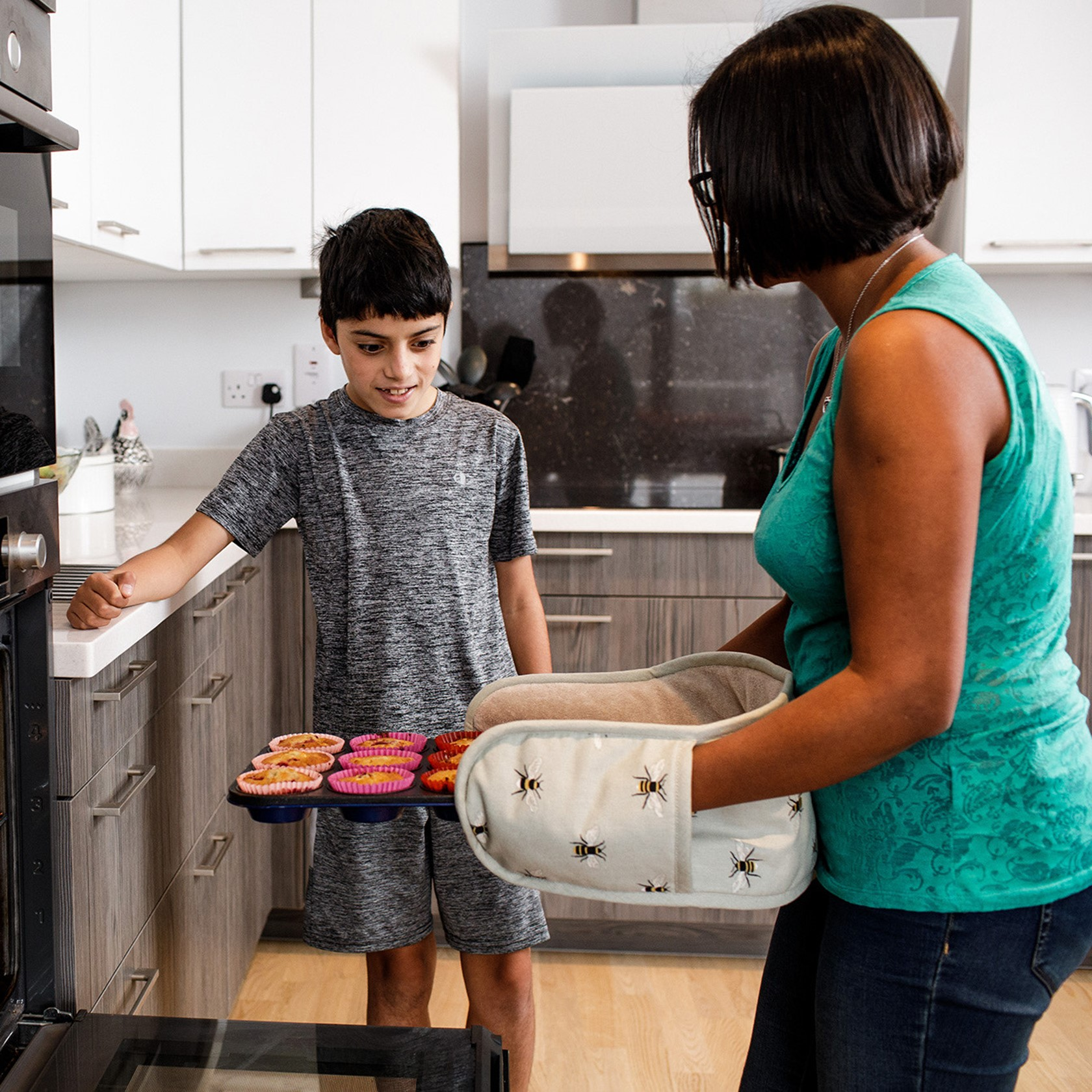 A mother removes her cupcakes from her electric oven as her son looks on.