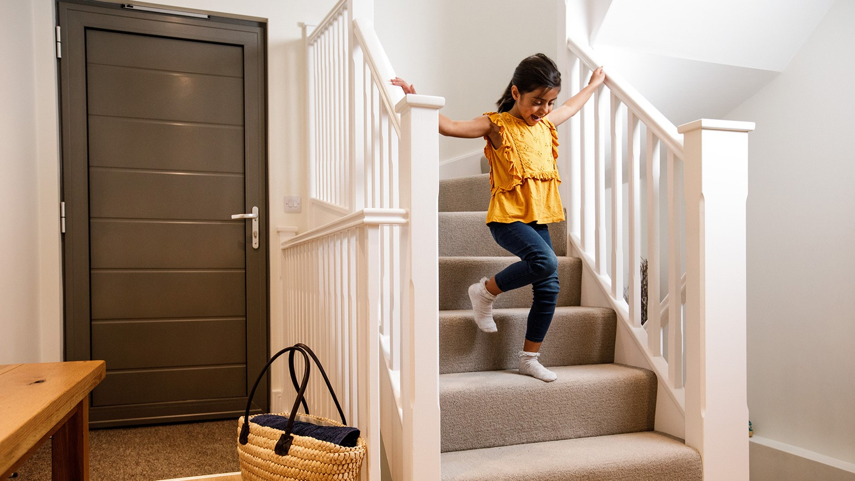 A young girl runs down the stairs in a modern electric home.
