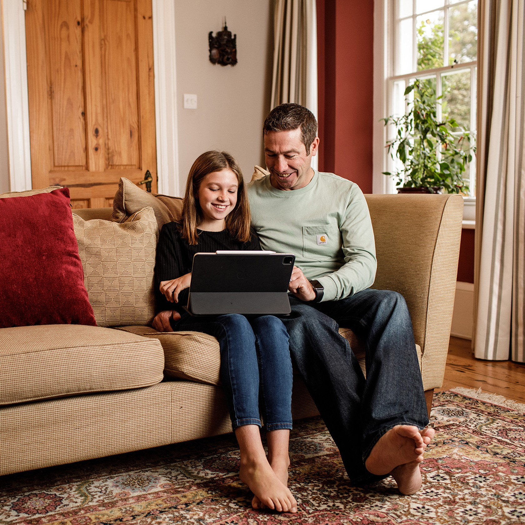 Father and daughter sit on a sofa whilst enjoying using a tablet.