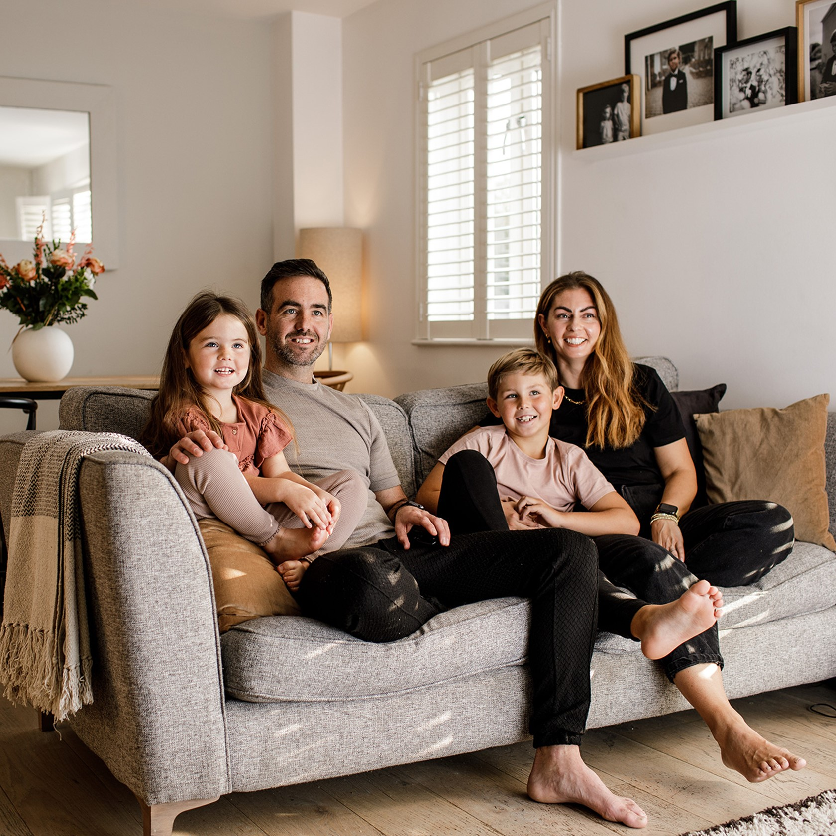 A family of four sit on the couch in their warm and cosy living room.