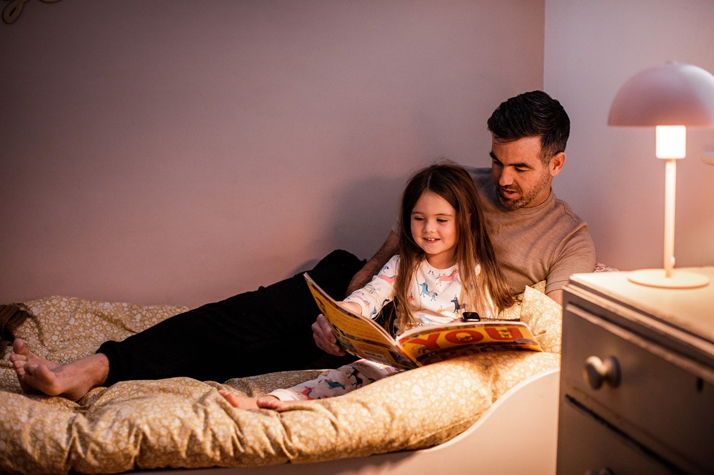 A father reads a story to his daughter in bed.